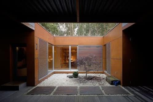 Moderna vivienda de madera en el bosque crecente y rosales for Patios modernos